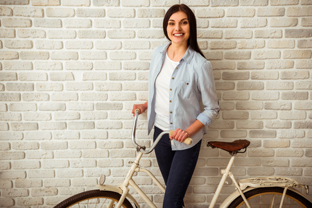 shorts t shirt sexy: Beautiful girl in casual clothes looking in camera and smiling while standing with a classical bike against white brick wall Stock Photo