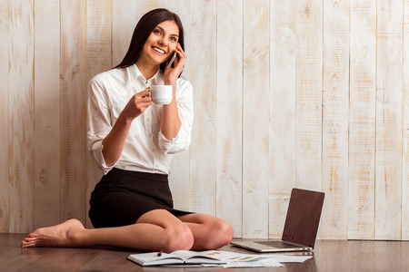 Beautiful girl in white shirt holding a cup, talking on the phone and smiling while sitting near laptop against wooden background