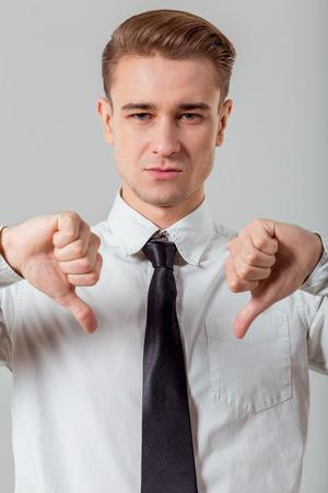 in  shirt: Retrato de hombre de negocios atractivo joven rubia en camisa cl�sica blanca y corbata oscura que muestra la muestra no est� bien, de pie contra el fondo gris