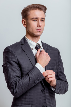 cufflink: Portrait of attractive young blond businessman in classical suit adjusting cufflink, standing with serious expression against gray background
