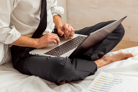 crosslegged: Attractive young businessman in white classical shirt and dark tie working and using laptop while sitting cross-legged on bed, close-up