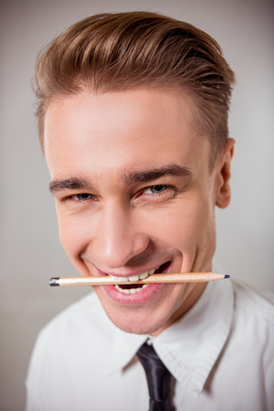Portrait of attractive young blond businessman in white classical shirt and dark tie smiling with pencil between his teeth, standing against gray background, close-up Stock fotó