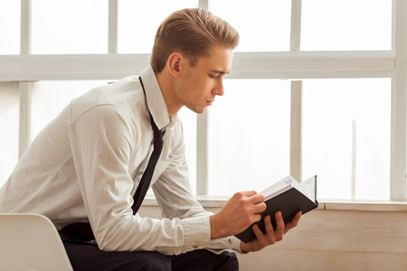 near side: Side view of attractive young blond businessman in white classical shirt and dark tie reading while sitting near the window in room Stock Photo