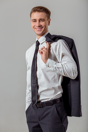 white suit: Portrait of attractive young blond businessman in classical suit smiling, looking in camera and holding jacket on finger behind his back, standing against gray background