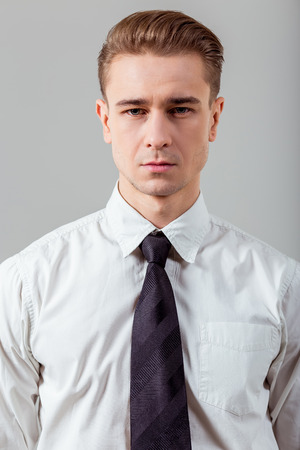 looking to camera: Portrait of attractive young blond businessman in white classical shirt and dark tie, standing against gray background and looking in camera