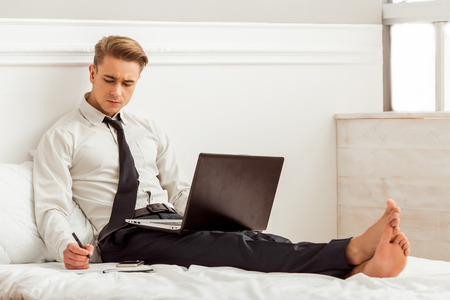 Attractive young blond businessman in white classical shirt and dark tie making notes and using laptop while sitting on bed