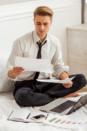 crosslegged: Attractive young blond businessman in white classical shirt and dark tie working and using laptop while sitting cross-legged on bed Stock Photo