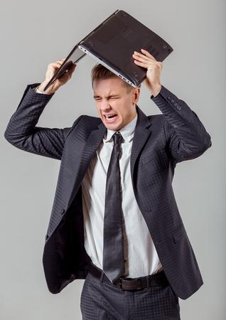 jefe enojado: Retrato de hombre de negocios atractivo joven rubia en traje cl�sico gritando y la celebraci�n ordenador port�til encima de la cabeza, de pie contra el fondo gris