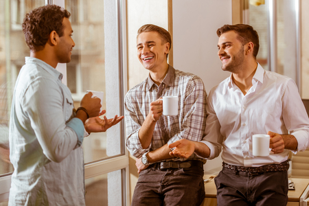 Three young handsome businessmen in casual clothes laughing, talking and drinking coffee while standing in office