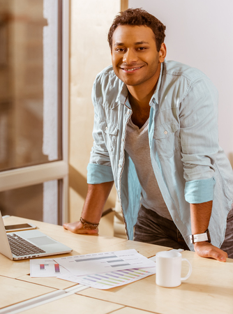 mulatto: Young handsome mulatto businessman in casual clothes smiling while working in office Stock Photo