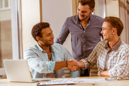 casual men: Three young handsome businessmen in casual clothes smiling and using laptop while working in office. Two men shaking their hands