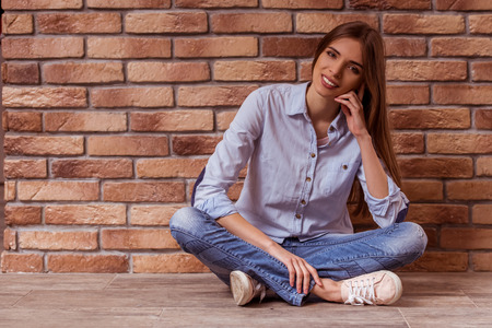 crosslegged: Beautiful young dark-haired girl in casual clothes posing, smiling and looking in camera, sitting cross-legged against brick wall
