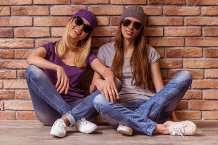 crosslegged: Two beautiful young girls in casual clothes and sunglasses posing and smiling, sitting cross-legged against brick wall Stock Photo