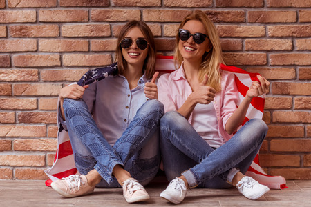 crosslegged: Two beautiful young girls in casual clothes and sunglasses posing, smiling, showing OK and holding American flag, sitting cross-legged against brick wall Stock Photo