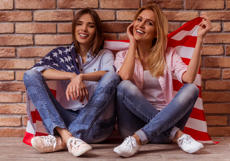 crosslegged: Two beautiful young girls in casual clothes posing, smiling and holding American flag, sitting cross-legged against brick wall
