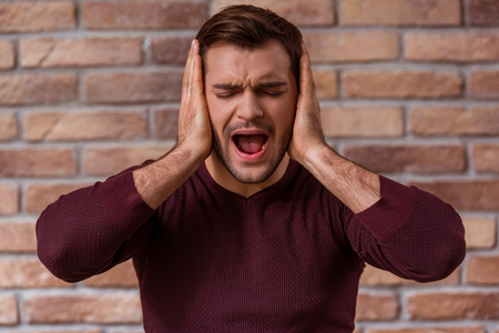 wall covering: Portrait of attractive young businessman in casual sweater showing emotions, covering his ears and screaming while standing against brick wall