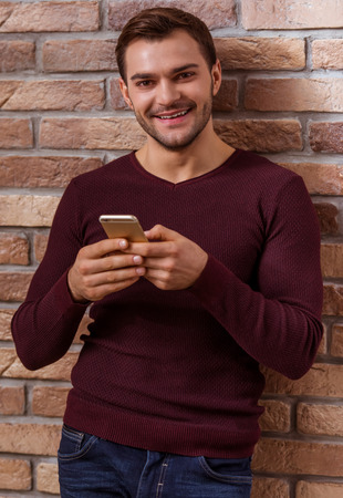 smiing: Portrait of attractive young businessman in casual sweater using a mobile phone, looking in camera and smiing while standing against brick wall