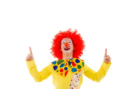 Portret van een grappige speelse clown in rode pruik wijzen en op zoek naar boven, geïsoleerd op een witte achtergrond Stockfoto