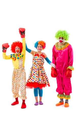 judging: Three funny playful clowns isolated on a white background. Two in boxing gloves: one won, another lost. Woman clown judging.
