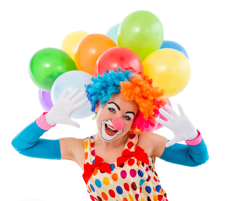 teasing: Portrait of a funny playful female clown in colorful wig teasing, looking at camera and showing palms, in the background balloons, isolated on a white