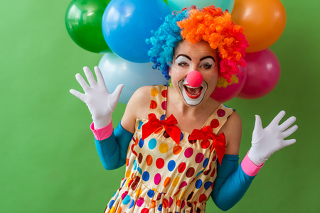 Portrait of a funny playful female clown in colorful wig teasng and showing palms, in the background balloons, standing on a green background