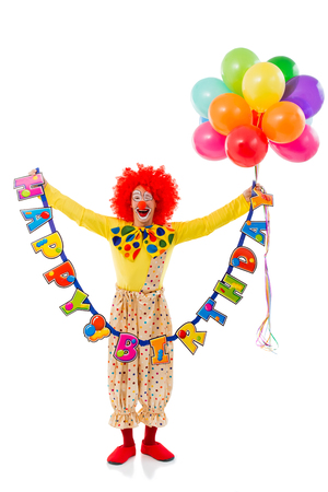 birthday celebration: Funny playful clown in red wig holding balloons and Happy Birthday garland, looking at camera and smiling, isolated on a white background Stock Photo
