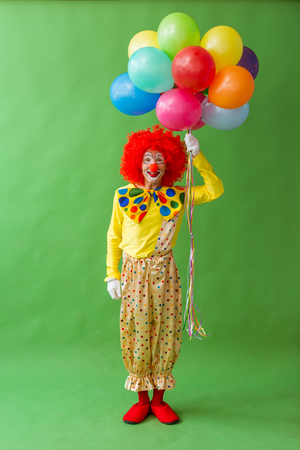 Funny playful clown in red wig holding balloons, looking at camera and smiling, on a green background
