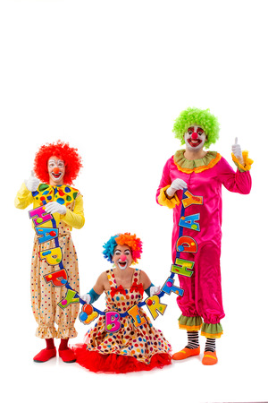 birthday adult: Three funny playful clowns holding Happy birthday garland, looking at camera and smiling isolated on a white background. Woman sitting, men showing OK sign.