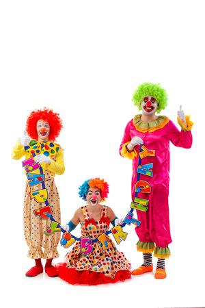 """caras felices: Tres payasos juguet�n divertido que sostiene la guirnalda """"feliz cumplea�os"""", mirando a la c�mara y sonriente aislados sobre un fondo blanco. Mujer sentada, los hombres que muestra signo de OK. Foto de archivo"""