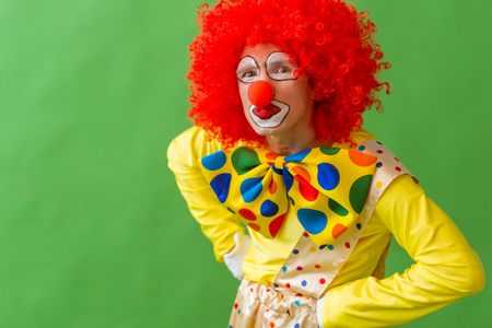 akimbo: Portrait of a funny playful clown in red wig standing akimbo and looking at camera, on a green background