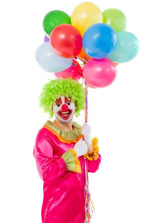 funny costume: Portrait of a funny playful clown in green wig holding balloons, looking at camera and smiling, isolated on a white background Stock Photo