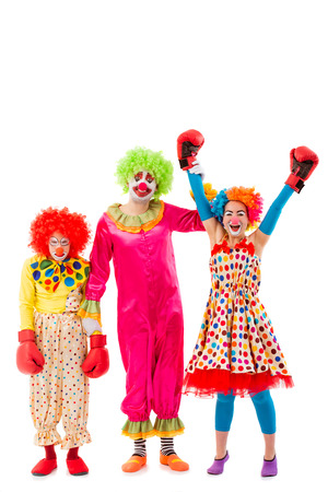judging: Three funny playful clowns isolated on a white background. Two in boxing gloves: woman won, man lost. One clown judging. Stock Photo
