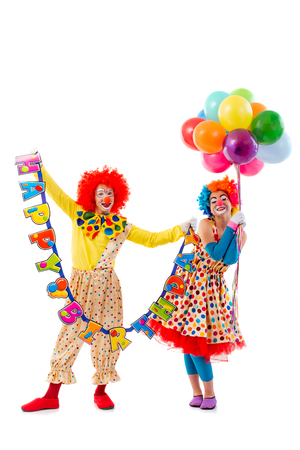 birthday adult: Two funny playful clowns looking at camera and smiling, isolated on white background. Man holding Happy birthday garland. Woman holding balloons. Stock Photo