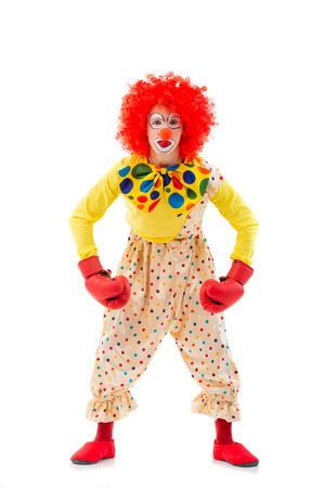 showing muscles: Funny playful clown in red wig and boxing gloves showing muscles and looking at camera, isolated on a white background Stock Photo