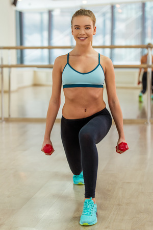 lunges: Attractive sport girl smiling and looking at camera while working out with dumbbells and doing lunges in fitness class