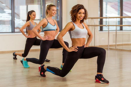 Tres muchachas del deporte atractivos que sonríen mientras que hace estocadas en la clase de gimnasia. Hermosa chica afroamericana mirando a la cámara Foto de archivo