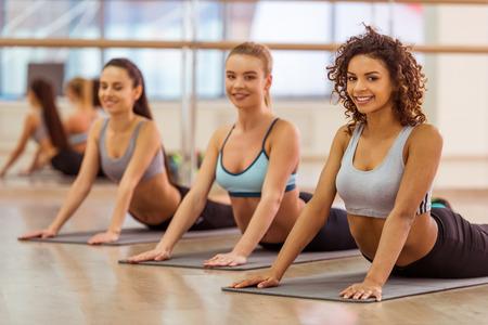 Tres muchachas atractivas del deporte que sonríen mientras que estira el cuerpo que miente en estera de la yoga en clase de la aptitud