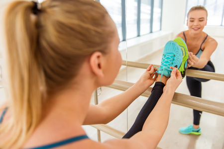 lithe: Attractive sport girl smiling and lacing training shoes while stretching the body in fitness class
