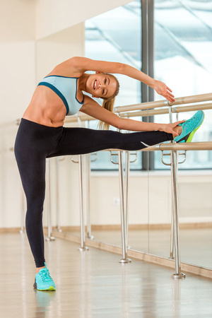 lithe: Attractive sport girl smiling and looking at camera while stretching the body in fitness class