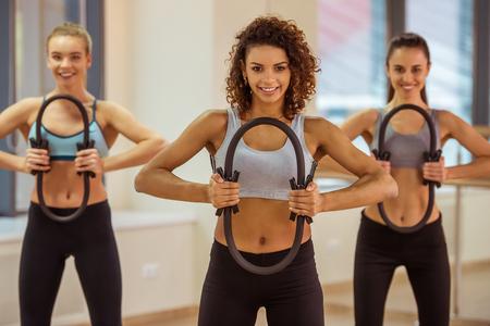 Drei attraktive Sport Mädchen lächelnd während der Arbeit aus mit Pilates Ring in Fitness-Klasse Standard-Bild - 54005576