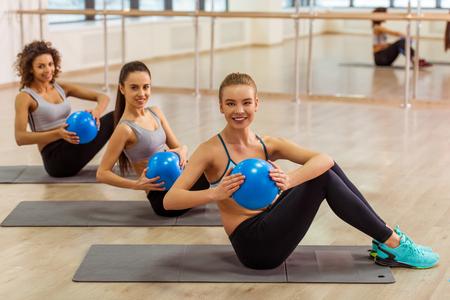 Drei attraktive Sport Mädchen lächelt, während er arbeitet mit Fitness-Ball auf Yoga-Matte in Fitness-Klasse sitzen Standard-Bild - 54005589