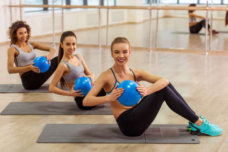 Three attractive sport girls smiling while working out with fitness ball sitting on yoga mat in fitness class