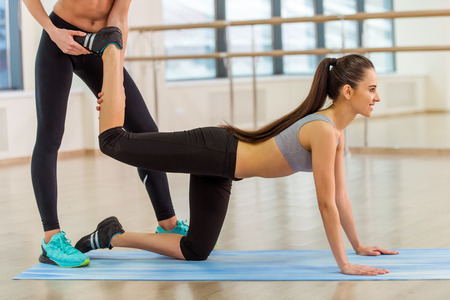 cropped out: Two attractive sport girls smiling while working out and stretching the body in fitness class, cropped