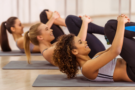 aerobic instructor: Side view of three attractive sport girls smiling while working out lying on yoga mat in fitness class Stock Photo