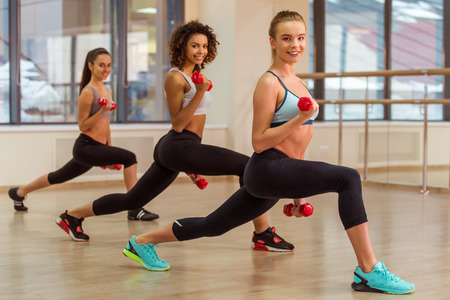 lunges: Three attractive sport girls smiling while working out with dumbbells and doing lunges in fitness class Stock Photo