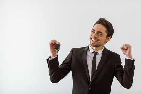 keys isolated: Happy handsome young businessman in classic suit smiling, looking away, holding keys and showing fist, on white background