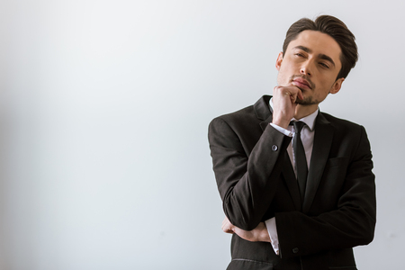 Thoughtful handsome young businessman in classic suit keeping hand on chin, on white background
