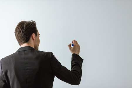 Back view of handsome young businessman in classic suit holding marker and writing, on white background Stock Photo