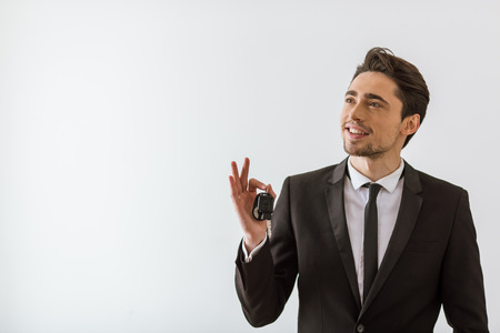 keys isolated: Handsome young businessman in classic suit smiling, looking away and holding keys, on white background