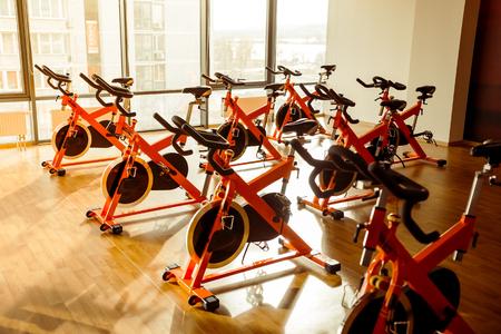 Des rangées de vélos d'exercice dans la salle de sport moderne attendent les gens à travailler sur Banque d'images